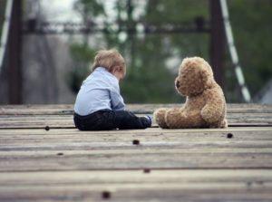 Baby boy sitting across from a brown teddy bear