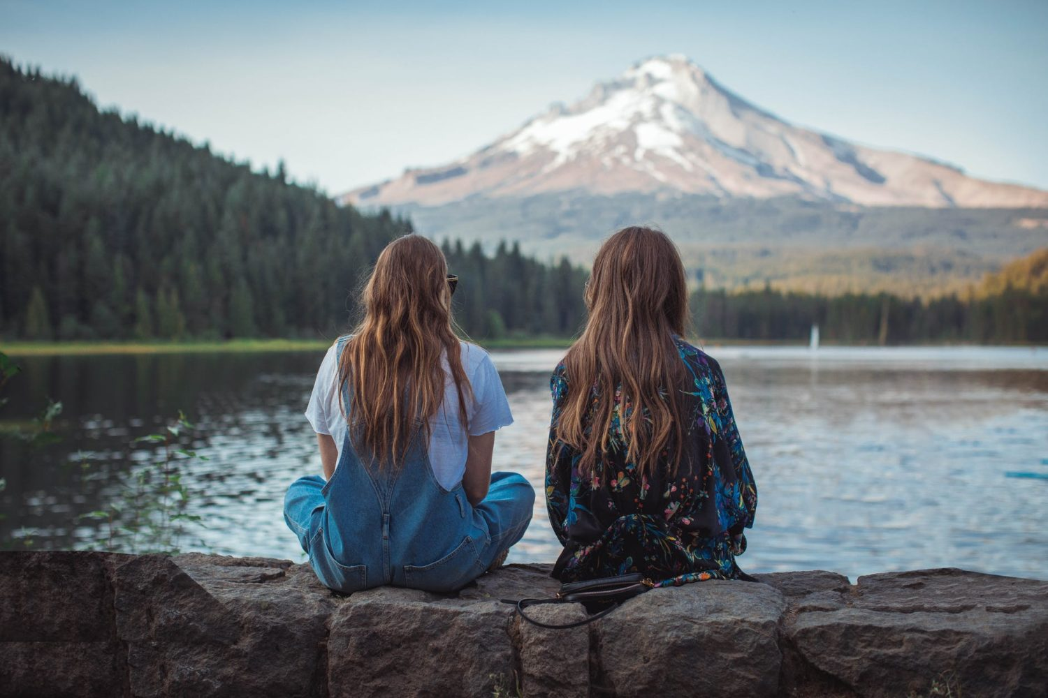 Two girls sitting on a ledge looking out towards the mountains