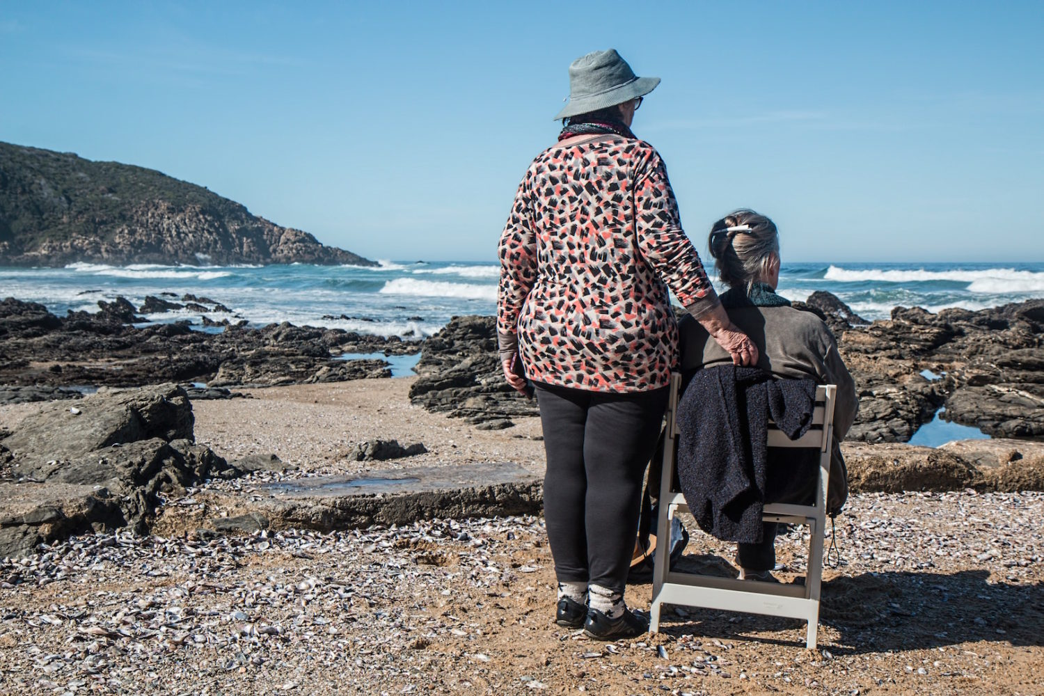 Two elderly people on the beach looking out towards the water; one is standing and one is seated
