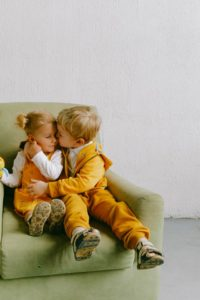 Young girl and boy wearing matching yellow outfits sitting on a green couch