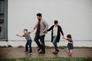 Family holding hands while walking down the street