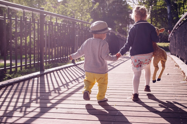 Young boy and young girl holding hands while walking on a bridge
