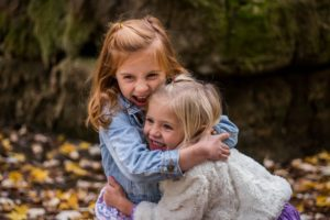 Two young girls laughing and hugging each other