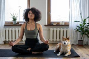 Female doing yoga, sitting on a yoga mat next to a dog