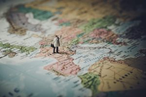 Miniature male figurine standing on a world map