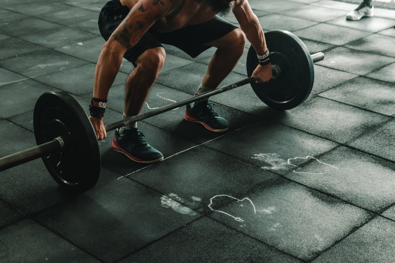 Man holding Barbell weights on the ground
