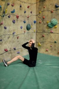 Man with hands on head in front of rock climbing wall