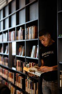Boy reading a book next to a book shelf full of books