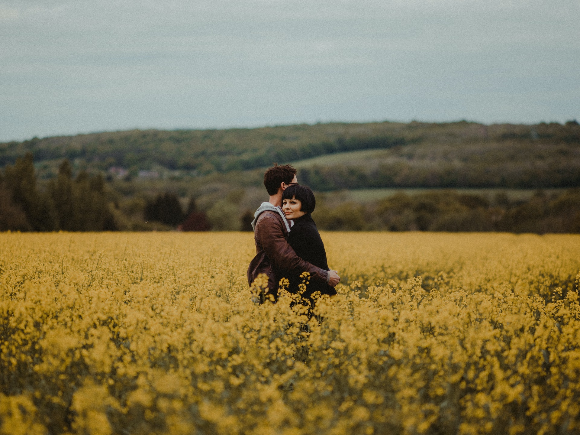 Male and female in a field of flowers hugging