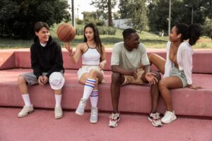 Group of teenagers sitting down at a basketball court