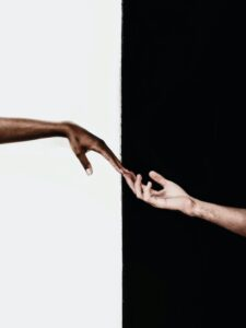 Black and white coloured hand touching