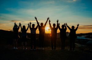 People facing the sunset with their arms up