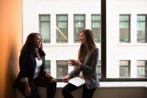 Two women talking by a window