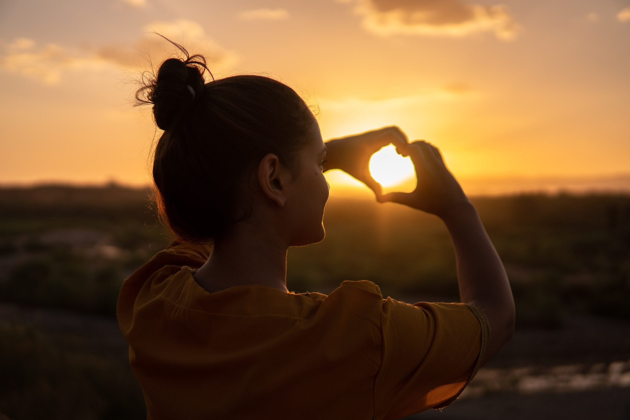 Women forming a heart shape with her hands in front of a sunrise