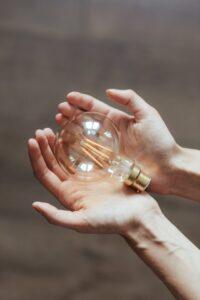 Light bulb being held hands