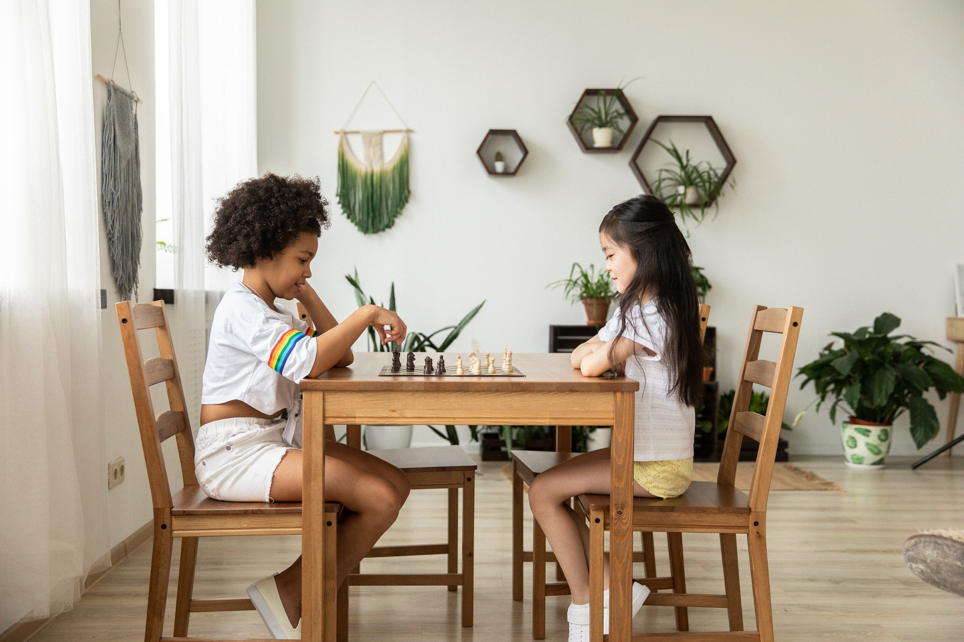 Two young girls playing chess