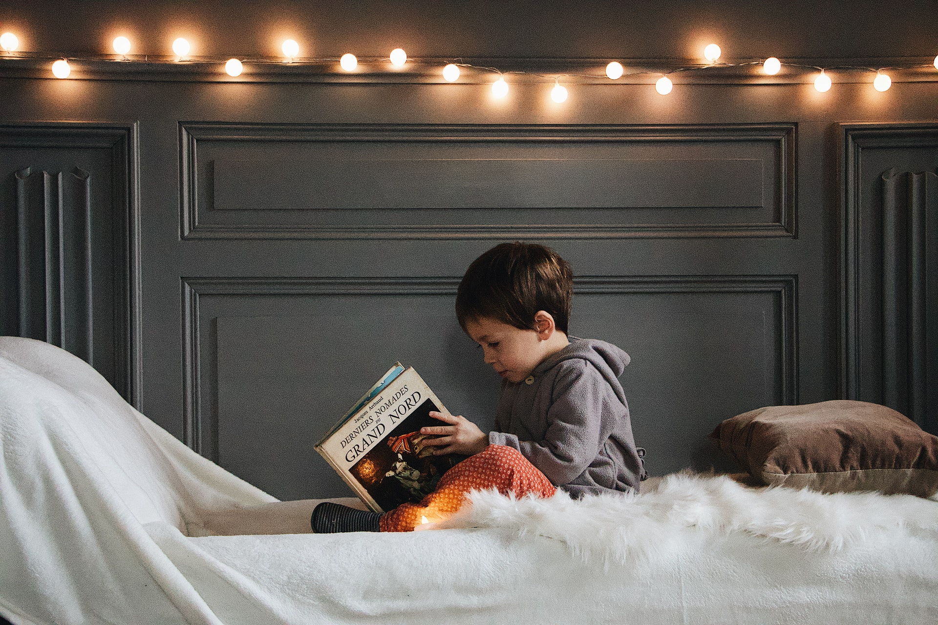 Young boy reading in bed