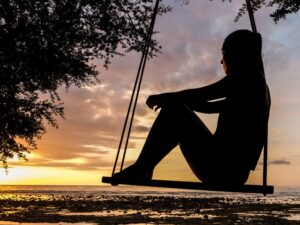 Female sitting on a swing, watching the sunset