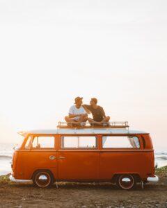 2 males sitting on a van