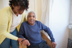 Elderly man in a chair and a young woman holding his arm.