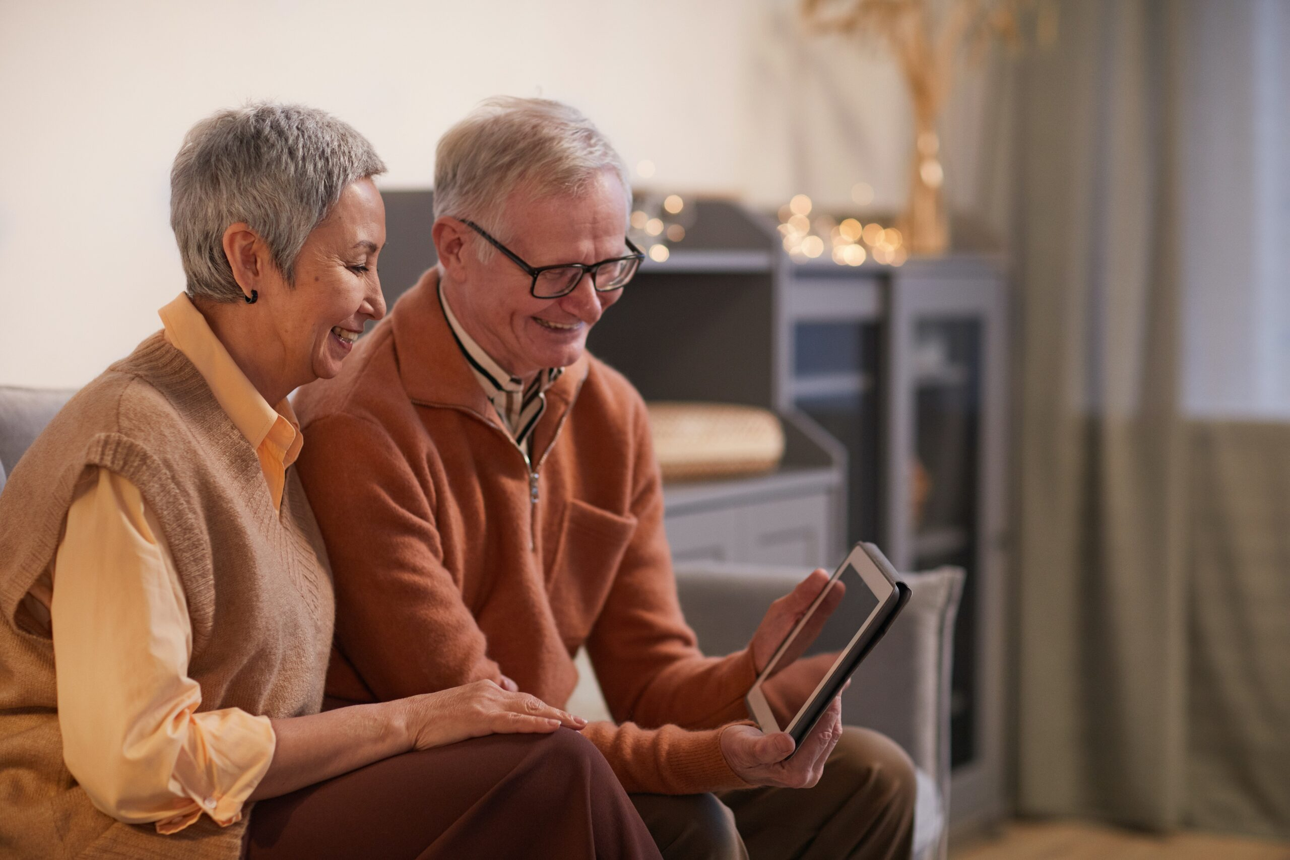 Elderly man and woman smiling at a tablet device.