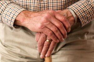 Elderly mans hands on a walking stick.