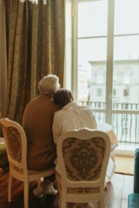 Elderly couple sitting in chairs and looking out the window.